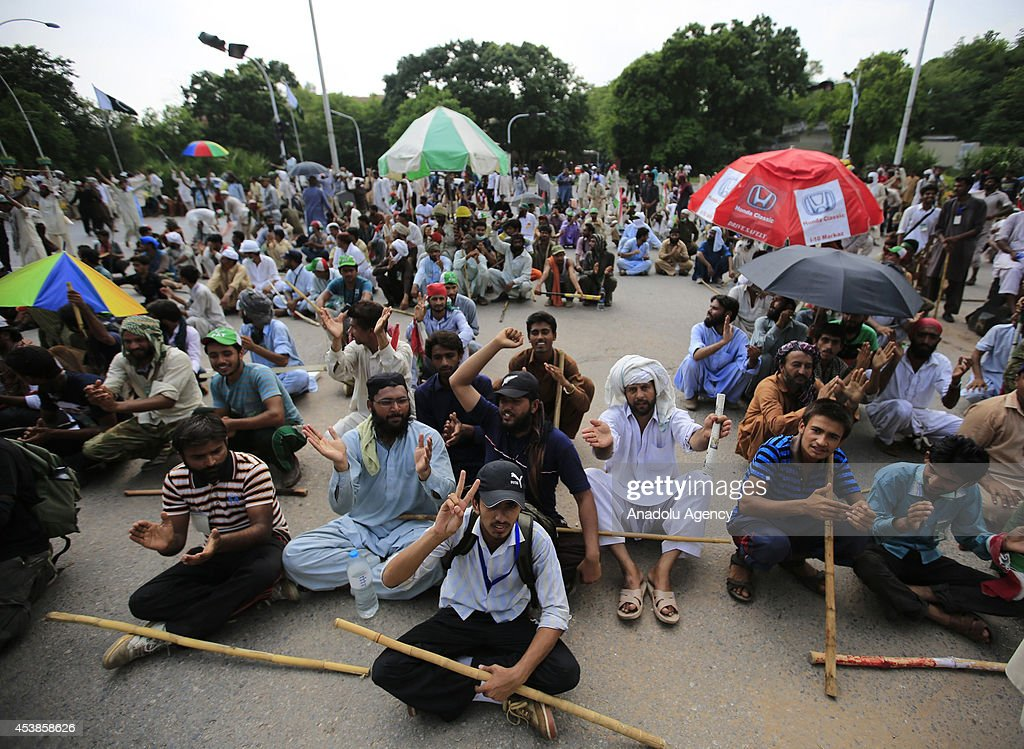 Followers of the Pakistan Tehreek-e-Insaf (PTI) and the Pakistan Awami Tehreek (PAT) parties enter Pakistani capital Islamabad's sensitive Red Zone area, which houses state buildings, on August 20, 2014. Thousands of protesters loyal to opposition politician Imran Khan and religious scholar Dr Tahir-ul-Qadri started their march on the parliament house after the two leaders asked their supporters to enter the Red Zone, a heavily protected area where many official and diplomatic buildings are located.