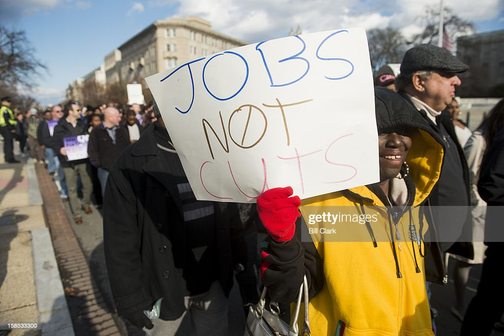 Following a rally in Upper Senate Park, protesters calling on Congress to reject cuts to Medicare and Medicaid as part of the fiscal cliff negotiations march past the Supreme Court hoping to reach the Capitol steps where they planned to leave coal for Speaker of the House John Boehner on Tuesday, Dec. 18, 2012. Capitol Police prevented the group from getting close to the Capitol steps.