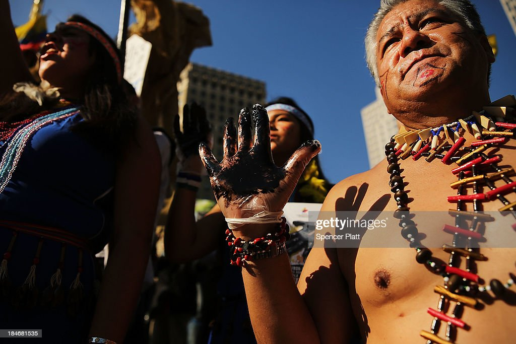 Following an $18 billion judgment against Chevron from a court in Ecuador protesters some in traditional dress and with black hands representing oil...