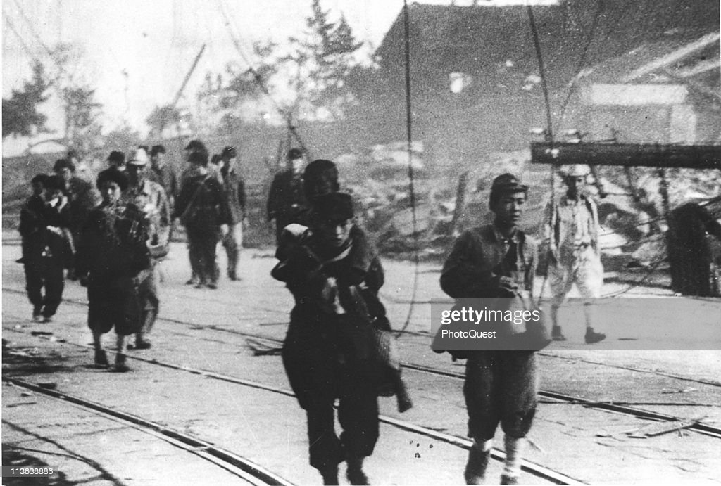 Following the atomic bombing of Nagasaki civilian and military survivors walk along a road inlaid with tracks Nagasaki Japan early August 1945 The...