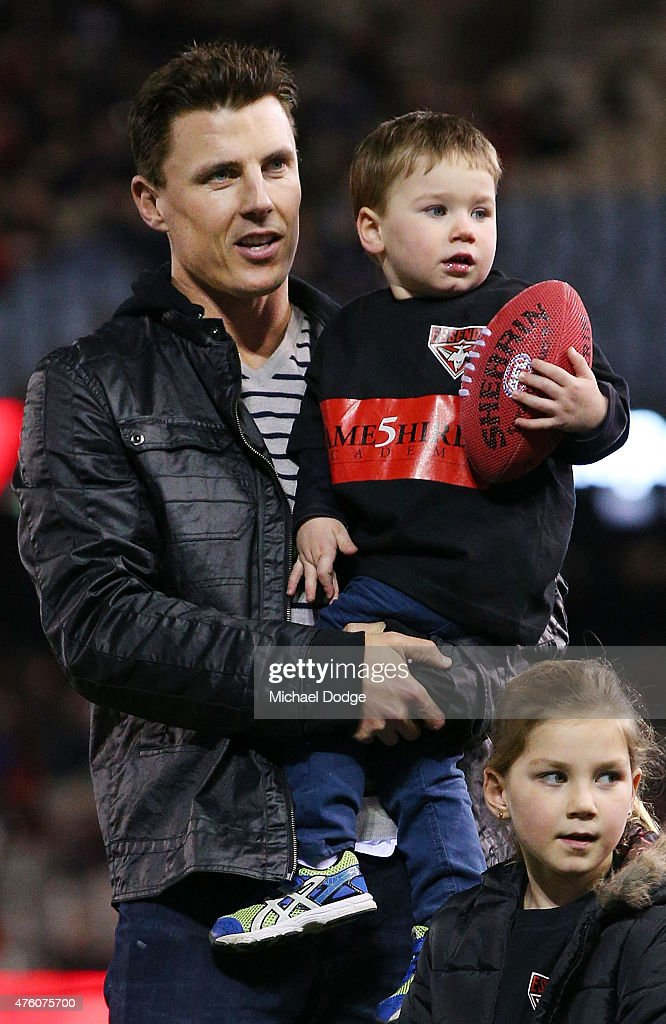 Fomer Bombers players Matthew Lloyd looks on with his kids as the players come out during the round 10 AFL match between the Essendon Bombers and the...