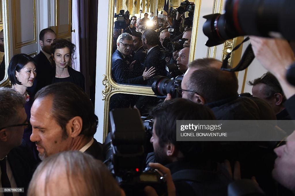 Fomer French Culture minister Fleur Pellerin (L) and newly appointed French Culture minister Audrey Azoulay (2L) are pictured by photographers at the Culture ministry in Paris on February 12, 2016 during the transferal of powers. Audrey Azoulay was named new French Culture minister as French President Francois Hollande reshuffled his cabinet on February 11, 2016, naming Jean-Marc Ayrault foreign minister and adding several ecologists to government as he seeks to widen his political base ahead of a presidential poll in 2017. AFP PHOTO / LIONEL BONAVENTURE / AFP / LIONEL BONAVENTURE