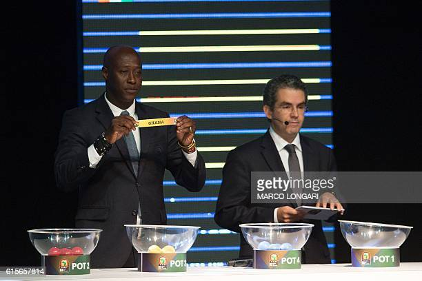 Fomer Senegalese football player Khalilou Fadiga shows a piece of paper bearing the name of Ghana next to Confederation of African Football secretary...