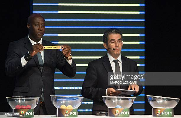 Fomer Senegalese football player Khalilou Fadiga shows a piece of paper bearing the name of Zimbabwe next to Confederation of African Football...