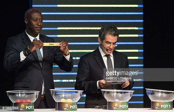 Fomer Senegalese football player Khalilou Fadiga shows a piece of paper bearing the name of Togo next to Confederation of African Football secretary...