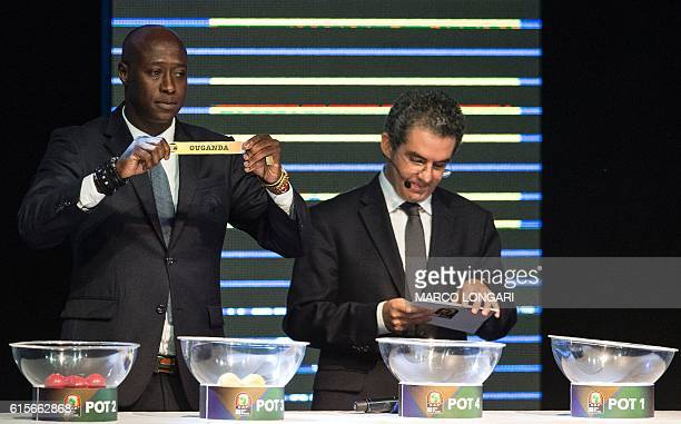 Fomer Senegalese football player Khalilou Fadiga shows a piece of paper bearing the name of Uganda next to Confederation of African Football...