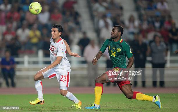Fongang Chedjou of Cameroon chases Amin Chermiti of Tunisia during the FIFA 2014 World Cup qualifier at the Stade Olympique de Radès on October 13...