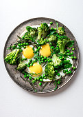 Fried eggs with broccoli and green peas and herbs: rosemary, arugula served on a silver plate on white surface.