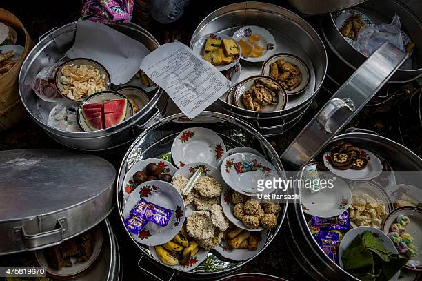 Food are seen inside of boxes know as 'tenong' as their eat together after praying during Nyadran ritual at Puroloyo Cemetery on June 4 2015 in...