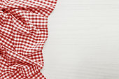 Food background, high angle view of white wooden table with red, folded, checkered tablecloth copy space
