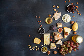 Food background with cheese. Blocks of moldy cheese, grapes, figs, honey, pear, dates, pickled prunes, nuts over on dark background. Copy space. Top view