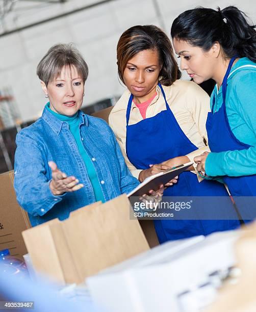 Food bank director instructing volunteers sorting donations