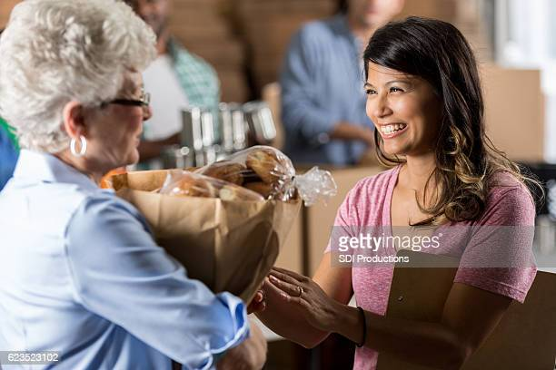 Food bank manager gives a woman groceries during food drive