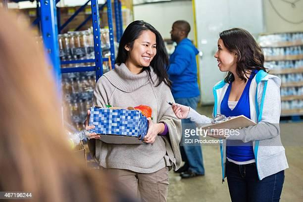 Food bank manager instructing volunteers in warehous