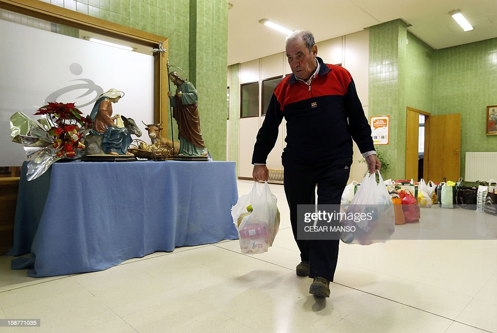 A Food Bank volunteer collects food donated by individuals, supermarkets and wholesalers in the national campaign to fight hunger in Spain in the warehouse of the Food Bank of Burgos in northern Spain on December 27, 2012. The Spanish Federation of Food Banks, established in 1987 in Barcelona to be retrofitted in all provinces of the country, last year distributed 104 million kilos of food for free. AFP PHOTO/ CESAR MANSO