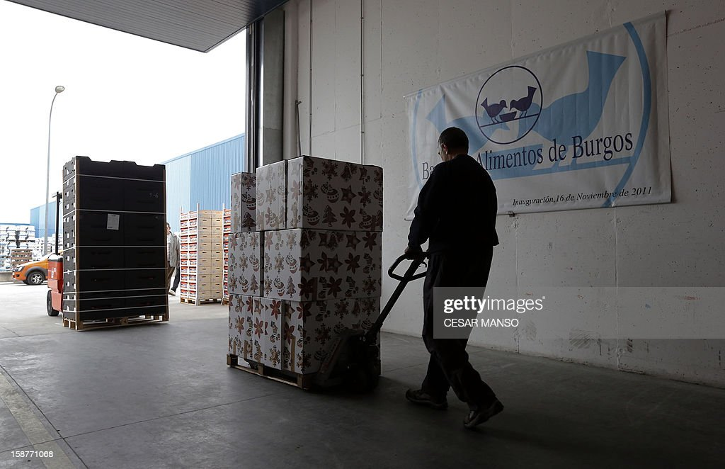A Food Bank volunteer moves food donated by individuals, supermarkets and wholesalers in the national campaign to fight hunger in Spain in the warehouse of the Food Bank of Burgos in northern Spain on December 27, 2012. The Spanish Federation of Food Banks, established in 1987 in Barcelona to be retrofitted in all provinces of the country, last year distributed 104 million kilos of food for free. AFP PHOTO/ CESAR MANSO