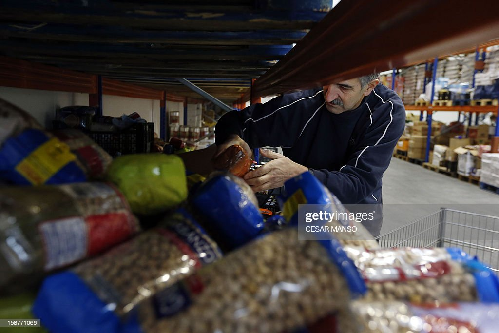 A Food Bank volunteer piles food donated by individuals, supermarkets and wholesalers in the national campaign to fight hunger in Spain in the warehouse of the Food Bank of Burgos in northern Spain on December 27, 2012. The Spanish Federation of Food Banks, established in 1987 in Barcelona to be retrofitted in all provinces of the country, last year distributed 104 million kilos of food for free. AFP PHOTO/ CESAR MANSO
