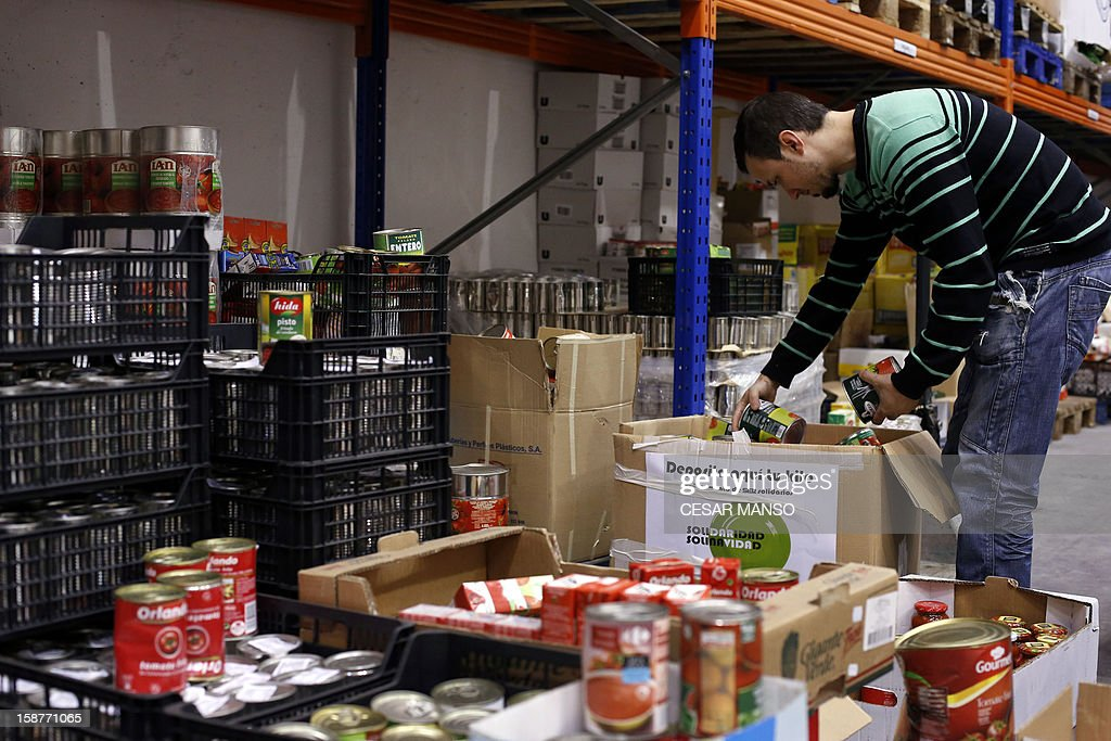 A Food Bank volunteer sorts food donated by individuals, supermarkets and wholesalers in the national campaign to fight hunger in Spain in the warehouse of the Food Bank of Burgos in northern Spain on December 27, 2012. The Spanish Federation of Food Banks, established in 1987 in Barcelona to be retrofitted in all provinces of the country, last year distributed 104 million kilos of food for free. AFP PHOTO/ CESAR MANSO
