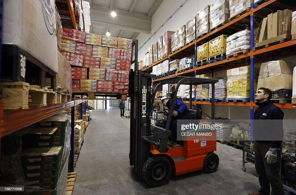 Food Bank volunteers forklifts food donated by individuals, supermarkets and wholesalers in the national campaign to fight hunger in Spain in the warehouse of the Food Bank of Burgos in northern Spain on December 27, 2012. The Spanish Federation of Food Banks, established in 1987 in Barcelona to be retrofitted in all provinces of the country, last year distributed 104 million kilos of food for free.