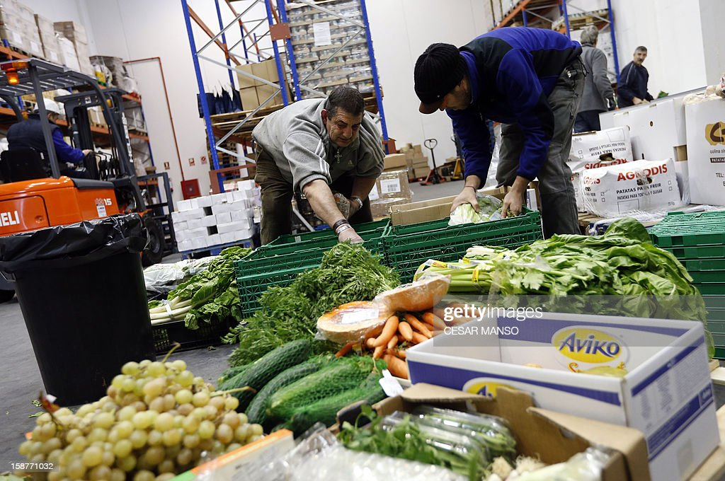 Food Bank volunteers sort food donated by individuals, supermarkets and wholesalers in the national campaign to fight hunger in Spain in the warehouse of the Food Bank of Burgos in northern Spain on December 27, 2012. The Spanish Federation of Food Banks, established in 1987 in Barcelona to be retrofitted in all provinces of the country, last year distributed 104 million kilos of food for free. AFP PHOTO/ CESAR MANSO
