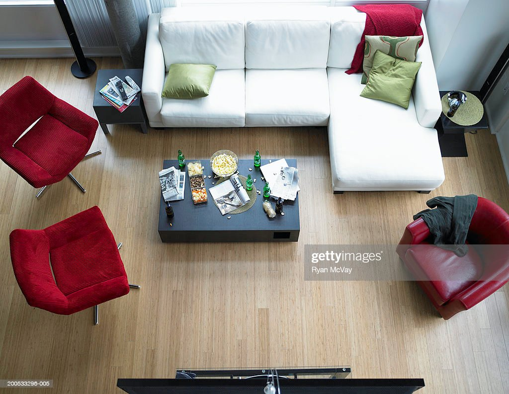 Food, beer and newspaper on coffee table in living room, elevated view : Stock Photo
