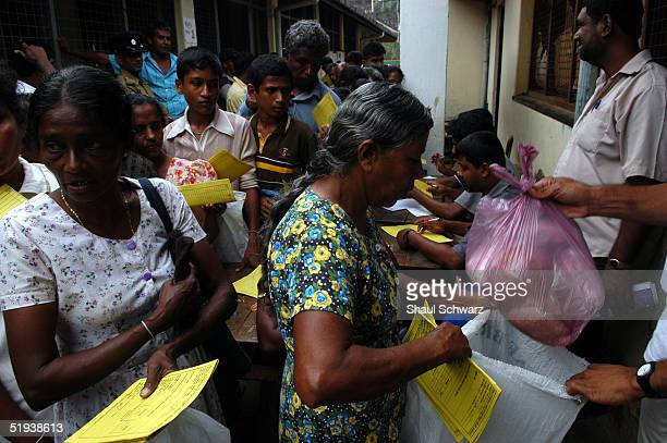Food being distributed at a refugee camp for tsunami survivors January 8 2005 in Matara Sri Lanka Two of the schools in town have turned been turned...