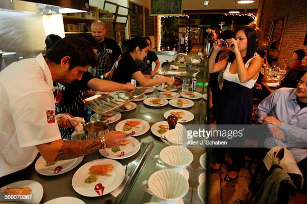 Food blogger Misty Oka right photographs Ludo Bites chef Ludo Lefebvre shown in white prapareing a dish at his pop–up restaurant during a pre–launch...