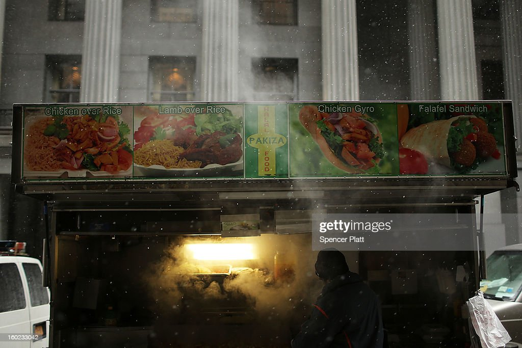 A food cart vendor cooks as it snows during the morning commute on January 28, 2013 in New York City. Following some of the coldest weather this winter, temperatures are expected to gradually warm during the week in New York.