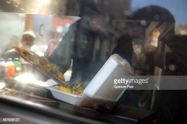 A food cart worker fills a styrofoam takeout container with food for a customer on December 19 2013 in New York City New York's City Council will...