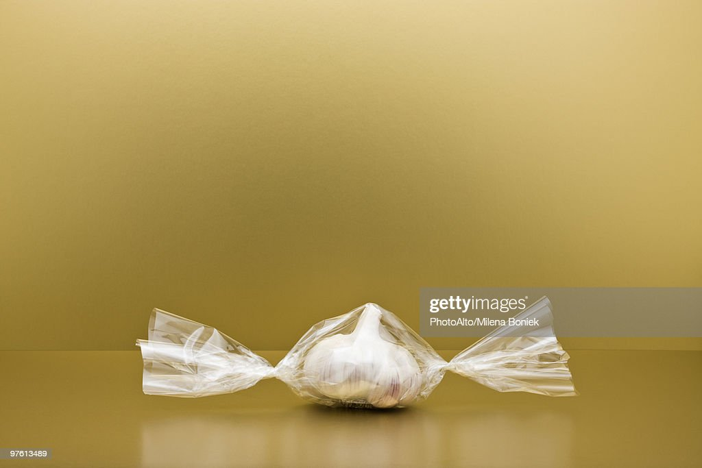 Food concept, head of garlic inside of cellophane candy wrapper