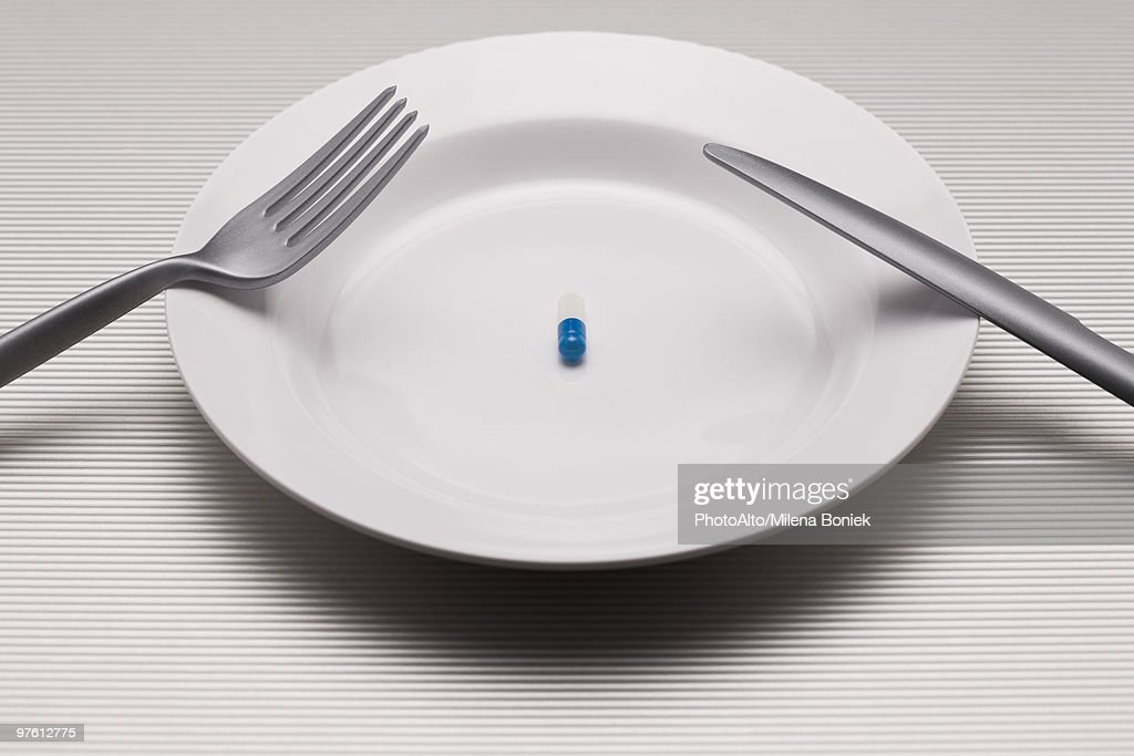 Food concept, single pill on plate