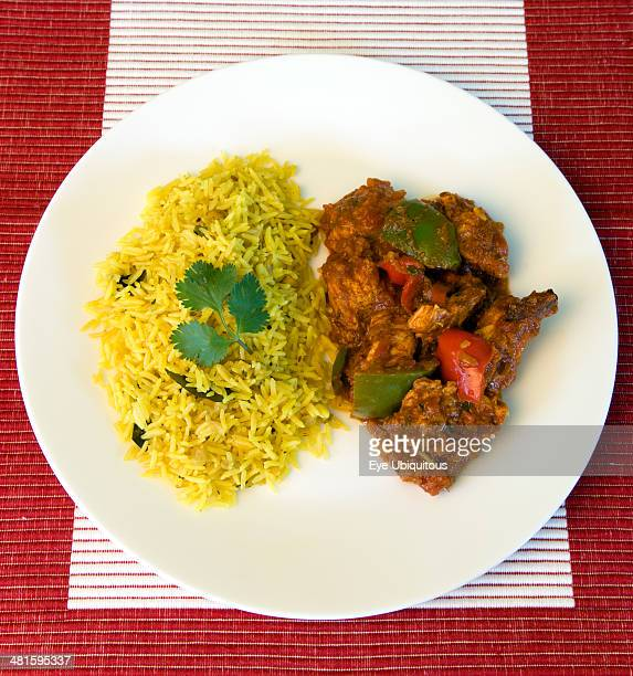 Food Cooked Curry Indian chicken Jalfrezi curry with yellow pilau rice on a white plate