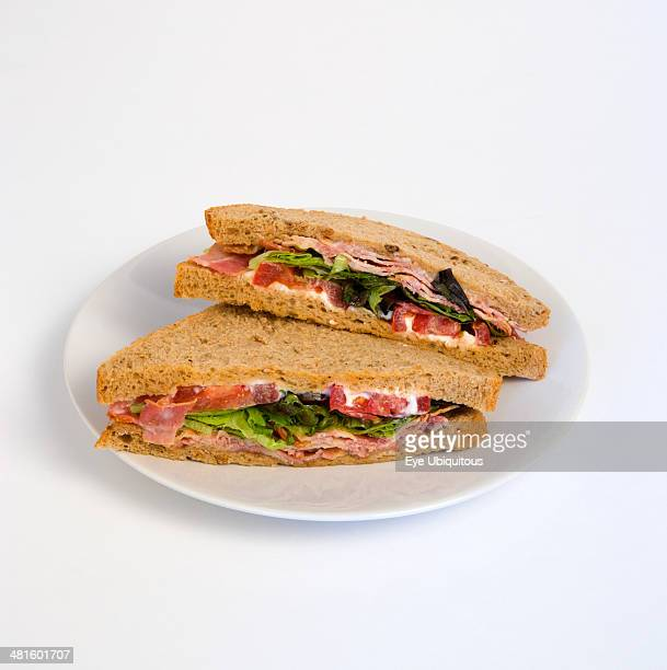 Food Cooked Sandwich Brown bread bacon lettuce and tomato BLT sandwich on a white plate against a white background