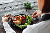 Decoration of chicken wings on wooden table. Chief prepares grilled spicy chicken with fresh vegetables. Over the shoulder view on food decoration.