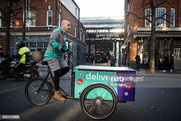 A food deliver cycle courier maneuvers his cargo bike as he prepares to collect an order for Deliveroo operated by Roofoods Ltd in London UK London...