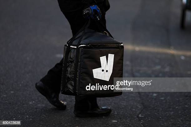 A food delivery courier carries a branded insulated bag as he prepares to deliver for Deliveroo operated by Roofoods Ltd in London UK on Thursday Dec...