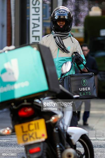 A food delivery courier holds an UberEats operated by Uber Technologies Inc insulated bag while wearing Deliveroo operated by Roofoods Ltd branded...