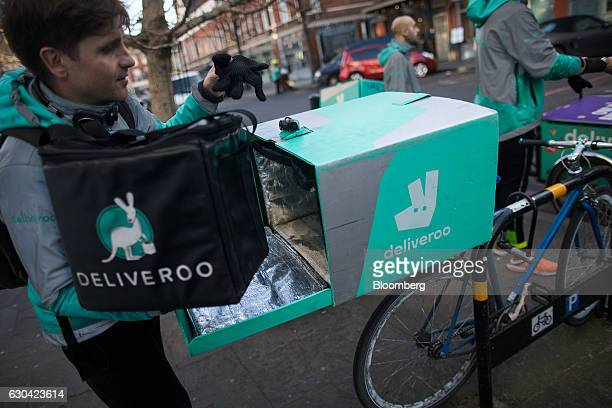A food delivery cycle courier places an insulated bag of food into the back of his bicycle as he prepares to deliver an order from Deliveroo operated...