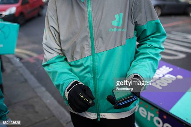A food delivery cycle courier uses his smartphone manufactured by Samsung Electronics Co Ltd to check an order from Deliveroo operated by Roofoods...
