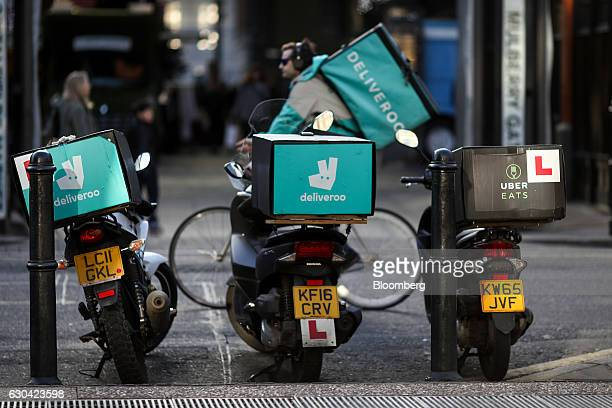 A food delivery cycle courier working for Deliveroo operated by Roofoods Ltd passes motor scooters with boxes for Deliveroo left and center and...