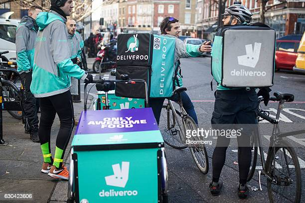 Food delivery cycle couriers chat as they wait for orders from Deliveroo operated by Roofoods Ltd in London UK on Thursday Dec 22 2016 The food...