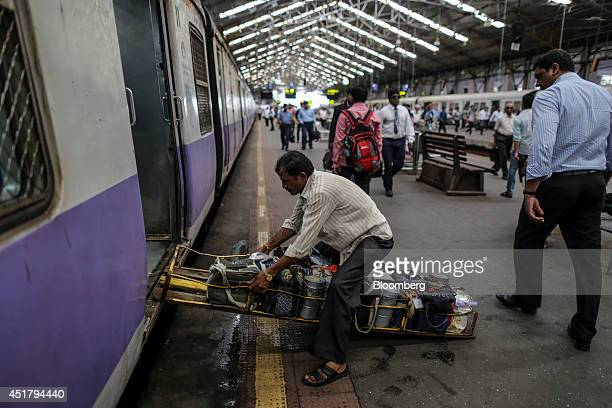 A food delivery man known as a dabbawala offloads lunch boxes from a commuter train as it sits on a platform at Churchgate Station in Mumbai India on...