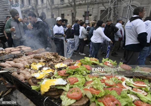 Food for sale is seen on a grill during a demonstration by trade unions in the Plaza de Mayo square in Buenos Aires on August 22 2017 against the...