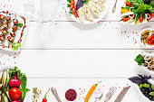 Food frame on white wooden table, free space. Top view on white wooden table with different snacks and copy space for text. Food, menu, cuisine concept