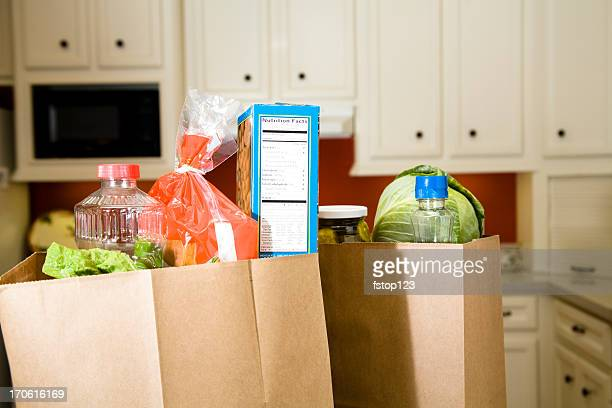 Food:  Grocery bags, sacks in home kitchen counter.