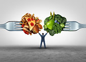 Food health decision and diet choice concept and nutrition options dilemma between healthy good fresh fruit and vegetables or greasy cholesterol rich fast food on a fork with a man in the middle uncer
