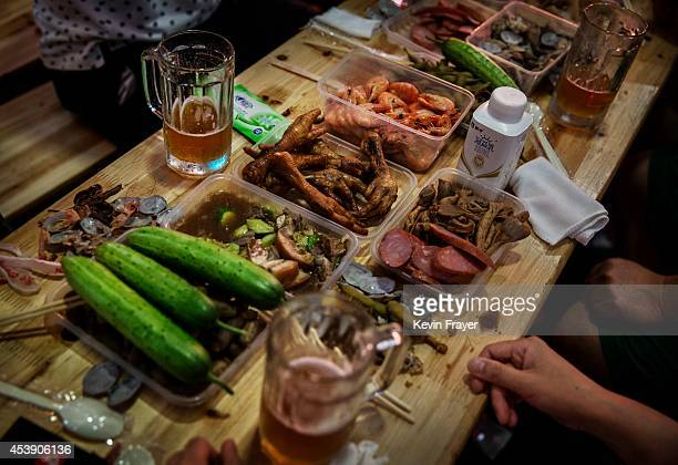 Food including the locally popular chicken feet is seen on a table at a beer hall during the 24th Annual Qingdao International Beer Festival on...