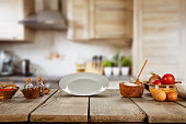 Food ingredients in kitchen placed on wooden plank. Empty plate, ideal for product placement. Very high resolution image
