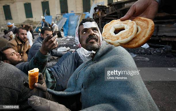 Food is offered to a wounded antigovernment protester who spent the night manning makeshift barriers protecting the antigovernment movement in Tahrir...