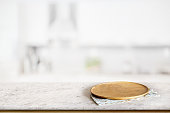 Empty round wooden plate or wooden dish on marble counter in blurred kitchen background. For food and product display montage.